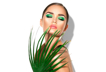 Beauty woman with natural green palm leaf. Portrait of model girl with perfect makeup, green eye shadows isolated