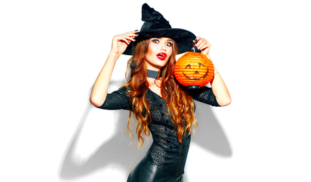 Halloween. Sexy witch with bright holiday makeup. Beautiful young woman posing in witches costume with pumpkin lantern