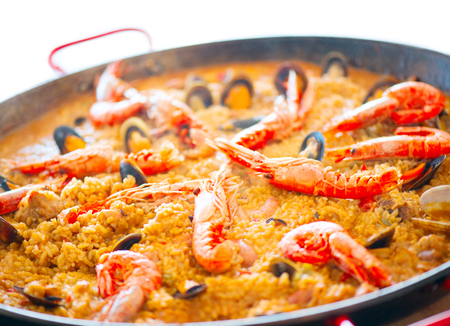 Paella. Traditional spanish food, seafood paella in the fry pan with mussels, king prawns, langoustine and squids isolated on white. Cooking paella