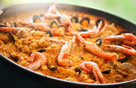 Paella. Comida tradicional española, paella de marisco en la sartén con mejillones, langostinos, cigalas y calamares. Cocinar paella al aire libre