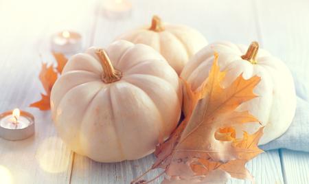 Dankzeggingsachtergrond. Vakantie scène. Houten tafel, versierd met pompoenen, herfstbladeren en kaarsen Stockfoto