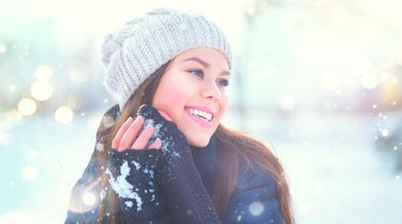 Winter girl portrait. Beauty joyful model girl enjoying nature, having fun in winter park. Beautiful young woman outdoors. Wintertime Standard-Bild