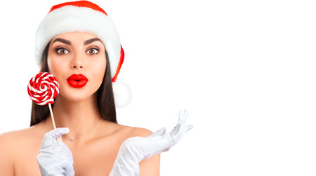 Christmas woman. Joyful model girl in Santas hat with lollipop candy pointing hand, proposing product. Sales. Surprised expression. Closeup portrait isolated on white background