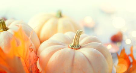 Thanksgiving-Hintergrund. Urlaub-Szene. Holztisch, dekoriert mit Kürbissen, Herbstlaub und Kerzen Standard-Bild