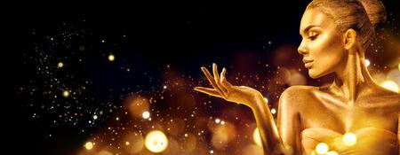 Mujer de Navidad de oro. Chica modelo de moda de belleza con maquillaje dorado, cabello y joyas apuntando con la mano sobre fondo negro Foto de archivo
