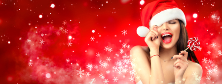 Christmas woman. Joyful model girl in Santas hat with red lips and lollipop candy in her hand. Closeup portrait over red background