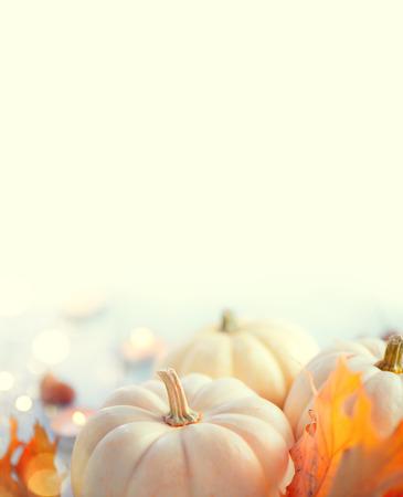 Thanksgiving-Hintergrund. Urlaub-Szene. Holztisch, dekoriert mit Kürbissen, Herbstlaub und Kerzen. Vertikales Bild