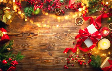 Scena Bożego Narodzenia. Kolorowe zapakowane pudełka na prezenty, piękne tło Boże Narodzenie i Nowy Rok z pudełkami na prezenty, bombkami, świecami i girlandą oświetleniową na tle drewnianego stołu. Widok z góry, flatlay
