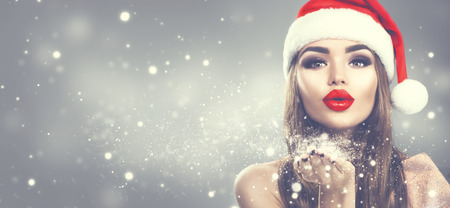 Christmas winter fashion girl on holiday blurred winter background. Beautiful New Year and Xmas holiday makeup. Beauty model woman in Santas hat blowing snow in her hand Stock fotó