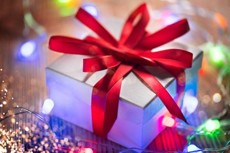 Weihnachtsfeiertag-Hintergrund. Eingewickelte Geschenkbox mit rotem Seidenband und bunter Lichtergirlande über Holzhintergrund. Kunstdesign für den Winterurlaub