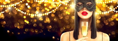Christmas and New Year holiday celebration. Beauty glamour woman celebrating with champagne, wearing carnival mask, drinking sparkling wine over holiday glowing background. Widescreen