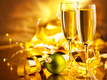 Christmas scene. Holiday champagne over golden glow background. Christmas and New Year celebration. Two flutes with sparkling wine over holiday bokeh blinking background Stock Photo