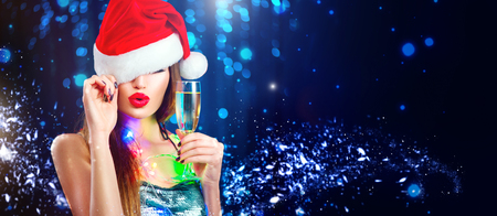Christmas sexy woman. Beauty model girl in Santa's hat with glass of champagne in her hand celebrating on blinking holiday winter wide background Stock Photo