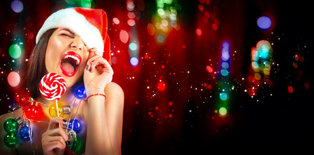 Christmas sexy woman. Beauty model girl in Santa's hat with with lollipop candy in her hand over blinking holiday background