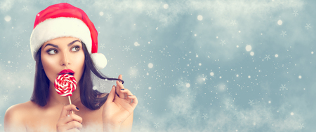 Christmas woman. Joyful model girl in Santas hat with red lips and lollipop candy in her hand. Closeup portrait over winter snow background