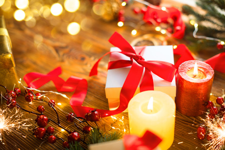 Christmas gift box with red satin ribbon and bow, beautiful Xmas and New Year backdrop with wrapped gift box, baubles, candles and lighting garland over wooden table background