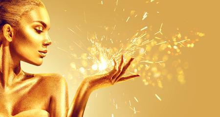 Donna d'oro con regalo magico di Natale. Bellezza modella ragazza con trucco dorato, capelli e gioielli su fondo oro gold