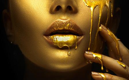 Goldene Farbflecken tropfen von den Gesichtslippen und der Hand, goldene Flüssigkeitstropfen auf dem Mund des schönen Modellmädchens, kreatives abstraktes Make-up. Schönheitsfrauengesicht Standard-Bild
