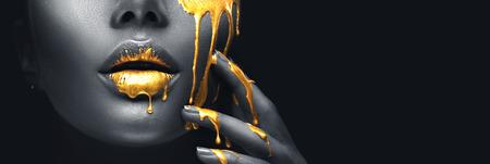 Manchas de pintura dorada gotean de los labios de la cara y la mano, gotas de líquido dorado en la boca de la chica hermosa modelo, maquillaje abstracto creativo. Rostro de mujer de belleza