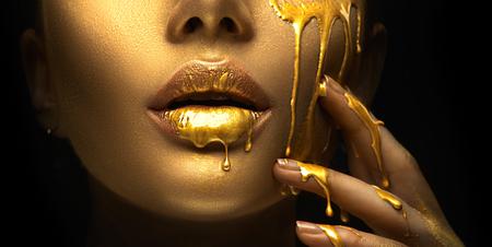 Macchie di vernice dorata gocciolano dalle labbra del viso e dalla mano, gocce di liquido dorato sulla bocca della bellissima modella, trucco astratto creativo. Volto di donna di bellezza Archivio Fotografico