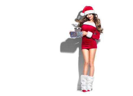 Beauty Christmas fashion model girl with Xmas gift boxes, wearing red Santa Claus dress and hat holding gifts. Sexy brunette young woman portrait Stock Photo