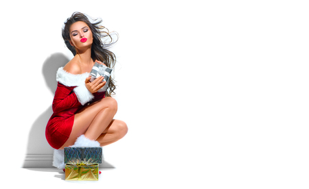 Sexy Santa. Beauty Christmas fashion model girl with Xmas gift boxes. Brunette young woman wearing red party costume holding gifts