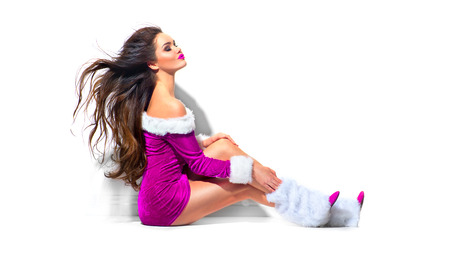 Sexy Santa. Beauty Christmas fashion model girl with blowing long curly hair. Brunette young woman wearing purple party costume