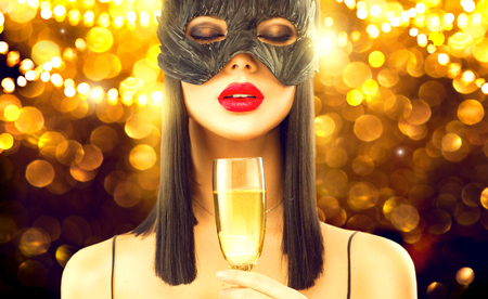 Christmas and New Year holiday celebration. Beauty glamour woman celebrating with champagne, wearing carnival mask, drinking sparkling wine over holiday glowing background