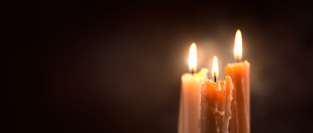 Candle flame closeup on a dark background. Candle light border design. Melted wax candles burning at night. Widescreen