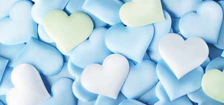 Valentines Day. Blue heart shape backdrop. Abstract holiday Valentine background with blue, green and white pastel colors satin hearts. Love concept. Flat lay, top view Stock Photo