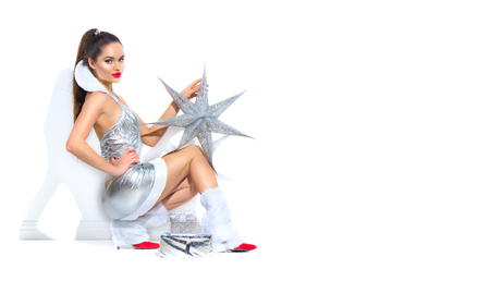 Beauty Christmas model girl in silver party costume holding Christmas star over white background. Beautiful young brunette woman in party sexy short dress posing in studio