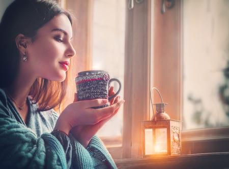 Piękna brunetka dziewczyna pije kawę w domu, patrząc przez okno. Zdjęcie Seryjne