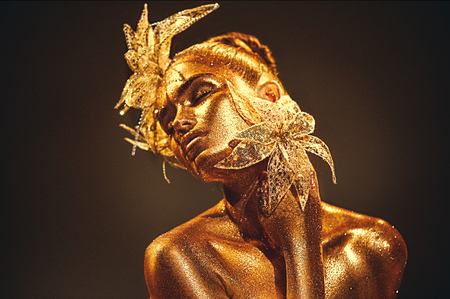 Fashion gold model woman with bright golden sparkles on skin posing, fantasy flower. Stock fotó