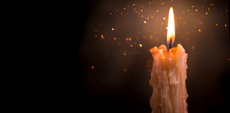 Candle flame closeup on a dark Banco de Imagens