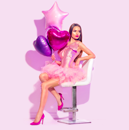 Beauty fashion model party girl with heart shaped air balloons posing, sitting on chair. Stok Fotoğraf