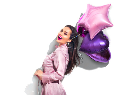 Beauty fashion model party girl with heart shaped air balloons having fun. Birthday party, Valentines Day. Beautiful young brunette woman over white background Foto de archivo