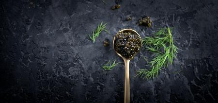 Schwarzer Kaviar in einem Löffel auf dunklem Hintergrund. Natürliche schwarze Kaviarnahaufnahme des Störs. Delikatessen. Ansicht von oben, flach Standard-Bild
