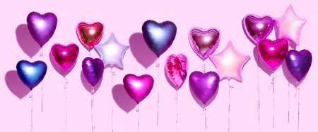 Air balloons. Bunch of purple heart shaped foil balloons, isolated on pink background. Valentines day background. Wide screen Stock Photo