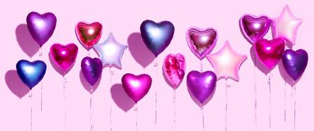 Globos de aire. Montón de globos de papel de aluminio en forma de corazón púrpura, aislado sobre fondo rosa. Fondo de San Valentín. Pantalla ancha Foto de archivo