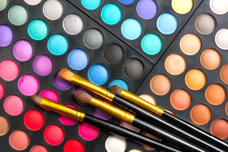 Insieme di trucco. Tavolozza e pennelli per ombretti multicolori professionali, colori vivaci e tinte di ombretti impostati sullo sfondo
