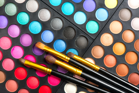 Makeup set. Professional multicolor make up eyeshadows palette and brushes, bright vivid colors and tints of eye shadows set background