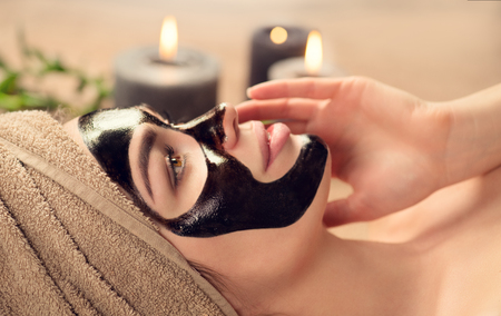 Beautiful woman with black purifying black mask on her face. Beauty model girl with black facial peel-off mask lying in spa salon. Skin care, acne treatment, cleansing skin. Peel of charcoal mask Stock Photo - 115942419