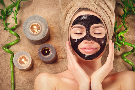 Beautiful woman with black purifying black mask on her face. Beauty model girl with black facial peel-off mask lying in spa salon. Skincare, cleansing Banco de Imagens