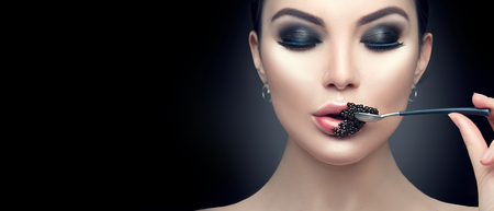Beautiful fashion model woman eating black caviar. Beauty girl with caviar on her lips isolated on black background Stockfoto