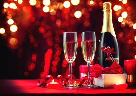 Valentine's Day romantic dinner. Champagne, candles and gift box over holiday red background. Wedding celebrating. Birthday party Standard-Bild