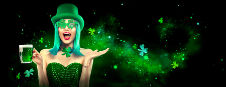St. Patrick's Day. Leprechaun model girl with pint of green beer over dark green background, decorated with shamrock leaves. Patrick Day celebration 版權商用圖片