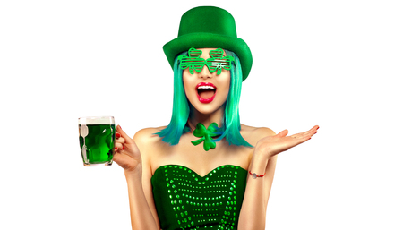 St. Patrick's Day. Leprechaun model girl with pint of green beer over white background. Patrick Day celebration