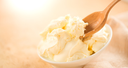 Mascarpone cream cheese close-up. Mascarpone Italian soft milk cream closeup, in wooden spoon. Homemade ice cream, yoghurt