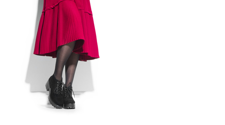 Woman fashion boots, elegant footwear. Young woman legs in suede black shoes. Red midi pleated skirt or dress wear Stock Photo