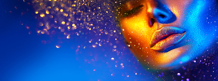 Fashion model woman face in bright sparkles, colorful neon lights, beautiful girl lips. Trendy glowing gold skin make-up